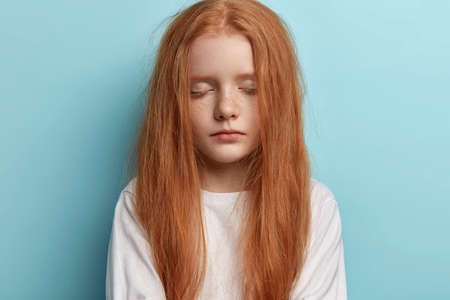 Close up shot of attractive redhead little girl keeps eyes shut, feels sleepy late in evening, waits for parents, has straight luxurious ginger hair, freckles on face, models over blue background.