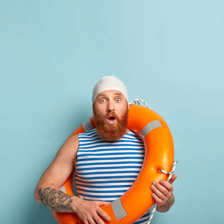 Emotional surprised blue eyed bearded male vacationist, recreats at seaside, keeps mouth opened, shocked with storm, wears swimhat, stands with lifebuoy, learns swimming. Summer time concept