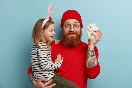 Gladful bearded father carries small daughter on hands, gives little decorative bunny, presents live pet to child, think out which name to give, stand over blue background. Childhood, domestic animals Imagens
