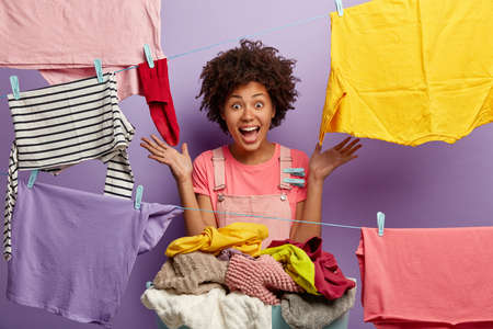 Cheerful dark skinned housekeeper hangs familys laundry to dry, surrounded with clotheslines, spreads palms sideways, hears something incredible, isolated on purple background. Day of washing