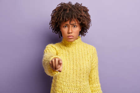 Displeased woman has Afro hairstyle, blames someone, points directly at camera, makes serious face, wears winter yellow sweater, stands against purple background. You are guilty in my misfortune