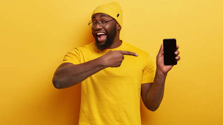 Delighted dark skinned male seller of modern devices, points at mobile phone with mock up black screen suggests buying gadget for low price wears yellow fashionable clothes in one tone with background