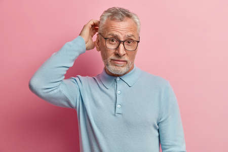 Shot of attractive bearded Caucasian man with thick grey stubble, scratches head in puzzlement, wears casual blue jumper and spectacles, isolated over rosy background, tries to solve problem Stock Photo