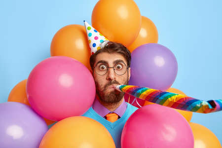 Good looking man has surprised face, blows into party horn, congratulates daughter with birthday, uses holiday attributes, poses against colorful balloons, enjoys celebration, shocked by something
