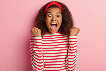 Energized upbeat African American woman triumphs and clenches fists, exclaims loudly, has curly dark hair, wears striped sweater, rejoices winning, poses against pink background, shouts hooray Фото со стока