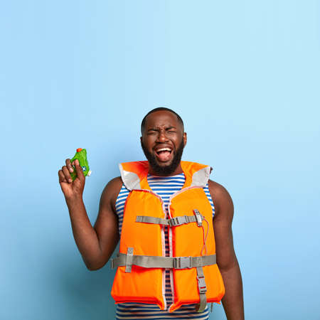 Depressed sorrowful black man feels unhappy to loose water battle game, holds toy gun, has frustrated expression, wears protective orange inflated lifevest, acts like child. Summer fun concept