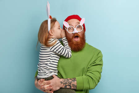 Small adorable female kid whispers secret to dad who has shocked expression to hear rumors from daughter, wear rabbit ears and spectacles, dressed in casual clothes. Childhood, secrecy concept