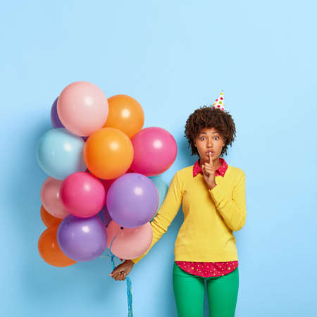 Shush, its secret. Beautiful Afro American birthday girl makes silence gesture, gossips with friends on party, tells information about organization of celebration, stands with airballoons indoor Banco de Imagens