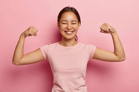 Strong powerful Asian woman with dark combed hair, toothy smile, raises arms and shows biceps, has piercing in ear, wears casual rosy t shirt, models against pink background. Look at my muscles