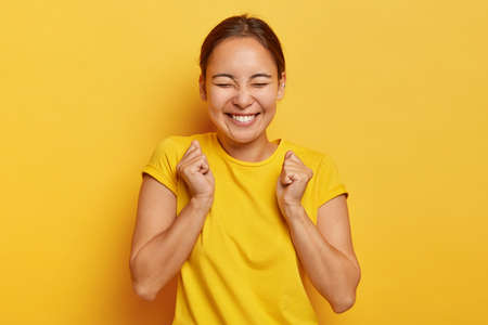 Yes, finally success. Joyful korean girl clenches fists with triumph, closes eyes from happiness and joy, has toothy smile, wears casual outfit, isolated on yellow background, triumphs victory