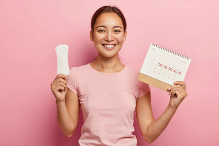 Adorable dark haired korean woman holds clean pad and menstruation calendar, has pleased face expression, happy to have regular menstrual cycle, wears pink t shirt. Women, hygiene, health care concept