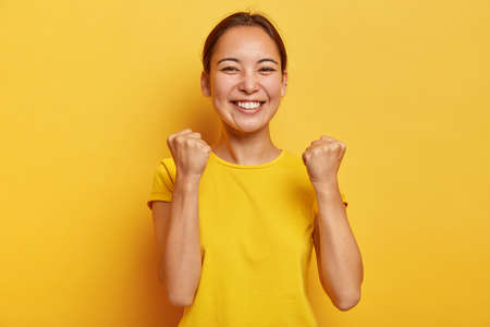Supportive good looking triumphs with success, raises clenched fists, smiles happily, has eastern appearance, happy finally gaining goal, glad to fullfil dream, dressed casually poses over yellow wall Фото со стока
