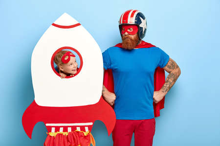 Serious brave man keeps hands on waist, wears red mask and cloak, protective helmet, looks at funny child who plays with toy handmade rocket, imagine being superheroes with supernatural power