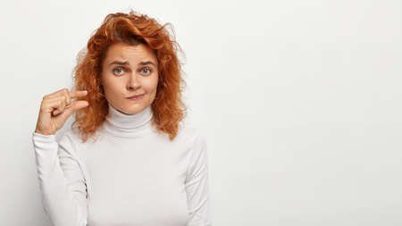 Redhaired woman shows something small with hand, demonstrates little ammount, demonstrates size of tiny object, purses lips and looks puzzled, wears casual turtleneck, copy space area aside.