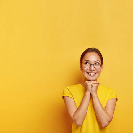 Vertical shot of cheerful thoughtful Asian female keeps hands pressed together under chin, hopes for something awesome, wears spectacles and t shirt, has natural beauty, isolated on yellow studio wall