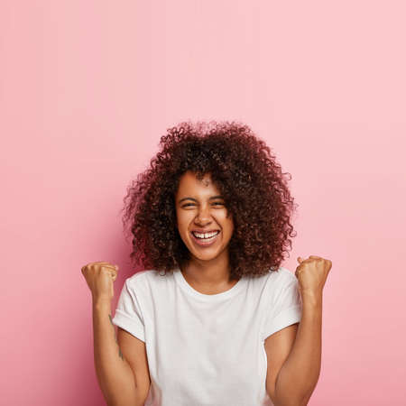 Excited joyous young cute woman raises clenched fists, stands without make up against pink background, has curly bushy hair, celebrates victory and triumph, wears white everyday t shirt. Oh yes
