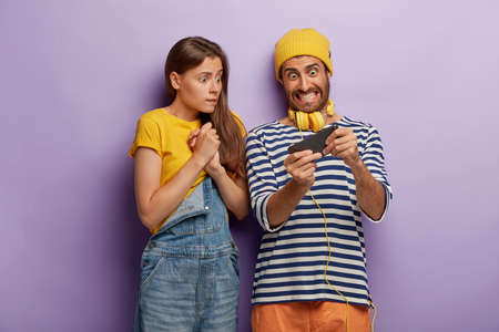 Obsessed couple play video game on smartphone, look nervously at display, eager to win, wear fashionable clothes, have worried excited expressions, isolated over purple background. Youth, addiction Stock fotó