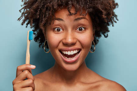 Close up shot of positive optimistic black woman holds toothbrush, being in good mood, has morning daily routine, shows nude shoulders, healthy dark skin isolated on blue. Dental care and teeth health
