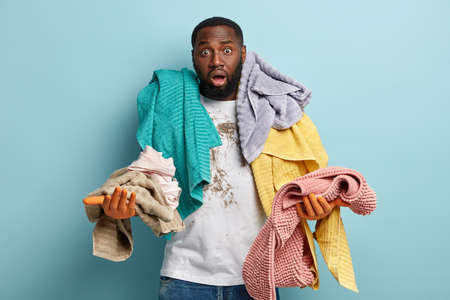 Isolated shot of indignant black ethnic man has bristle overloaded with laundry, stares with bugged eyes and opened mouth, has dirty t shirt, models over blue background. Householding concept