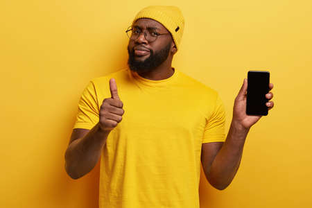I recommend buying this gadget. Satisfied black unshaven man hods modern cell phone, shows thumb up, really likes device, looks assertive, wears yellow hat and t shirt in one tone with background