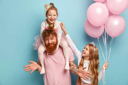 Two funny naughty sisters play together, tickle each other being cared by dad. Cute little girl holds bunch of air balloons. Happy family of father and two daughters prepare for holiday, pose indoor Stock Photo