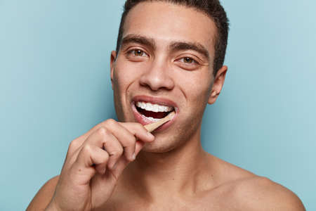Smiling young man with healthy teeth, holds toothbrush, cares of dental hygiene, looks pleased, has dark eyes, short hairstyle, muscular body, isolated over blue studio wall. Daily routines.
