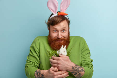 Horizontal shot of satisfied blue eyed bearded guy feeds small white rabbit with green grass, loves pet, wears casual jumper, bunny ears, looks gladly at camera, cares about animal, stands indoor