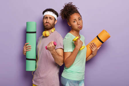 Displeased mixed race couple stand back to each other, raise heavy dumbbells, feel tired afer active sport workout in gym, use karemat, wear casual t shirts, need to take rest, isolated on purple wall Stock Photo