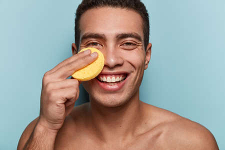 Handsome young guy holds face pad on face, smiles broadly, does facial treatments, enjoys soft skin after having shower, poses with bare shoulders, isolated over blue background. Body care concept