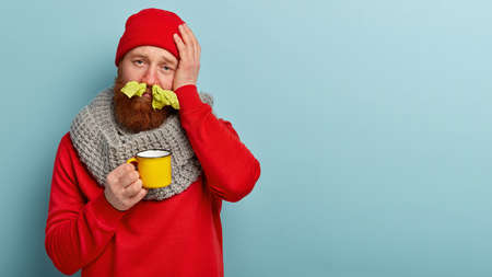 People, illness and treatment concept. Dissatisfied bearded man stucks noses with tissues, has headache, caught cold, running nose, drinks hot drink, sneezes and has terrible migraine poses indoor