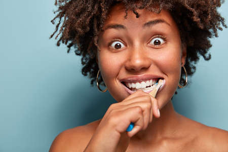 Headshot of emotional surprised dark skinned pretty woman with curly hair, wants to have healthy white teeth, brushes with toothpaste and toothbrush, looks with bugged eyes, shocked to oversleep