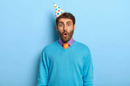 Portrait of shocked unshaven guy wears party hat, blue sweater with purple shirt and tie, surprised to be late on party, celebrates getting new job position with colleagues isolated on blue background