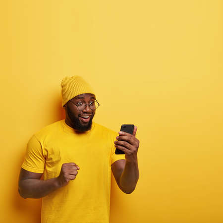 Overjoyed Afro man with thick bristle, looks happily at cell phone, feels upbeat, celebrates good news, keeps clenched fist, wears yellow stylish hat, t shirt, models in studio, blank space upwards