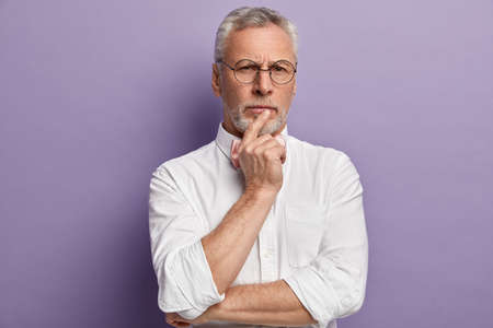 Strict senior man has clever thoughtful expression, keeps hand near mouth, wears spectacles and white shirt models over purple background, contemplates about future plans. People and age concept