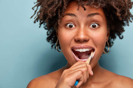 Dental hygiene and dentistry concept. Headshot of surprised young Afro American woman with crisp hair, uses toothbrush and toothpaste for cleaning teeth, stares with bugged eyes isolated on blue