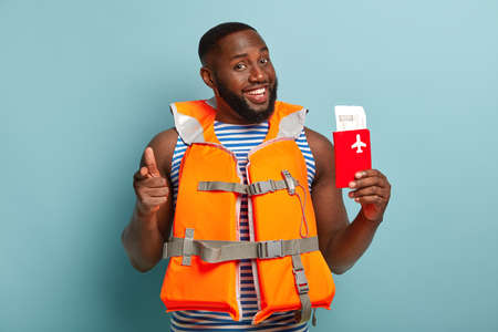 You should join our trip. Glad smiling unshaven dark skinned man holds boarding ticket and passport, wears lifejacket, uses personal floation device, points at camera, suggests having nice journey Stock fotó