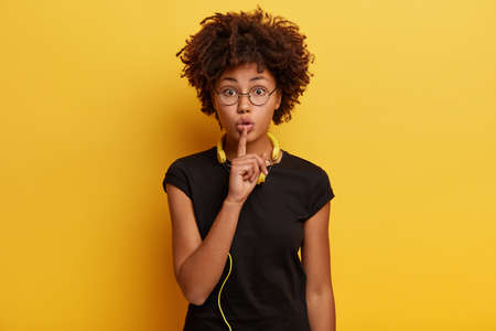 Shush, dont spread rumors. Secret black young woman makes hush gesture, enjoys audio track in modern yellow headphones, asks not tell which style of music she prefers. Leisure and hobby concept Banco de Imagens
