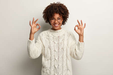 Approval and agreement concept. Picture of happy black ethnic woman makes okay gesture with both hands, says everything is super or perfect, dressed in white jumper, proceeds according to plan Archivio Fotografico