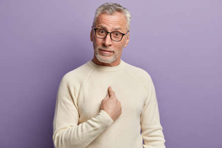 Are you talking about me. Bearded senior man points at himself with bewilderment, asks if he did something wrong, wonders, wears casual white jumper and spectacles, isolated over purple background