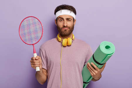 Isolated shot of serious man ready for playing tennis during pastime, holds racket and karemat, listens music, recreats actively, enjoys hobby, has confused facial expression. Sport concept.