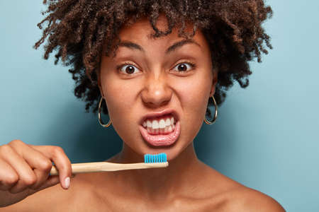 Portrait of healthy girl brushes teeth, holds wooden brush, has morning routine, curly hair, poses indoor over blue background, shows bare shoulders awakes early. People, ethnicity and hygiene concept