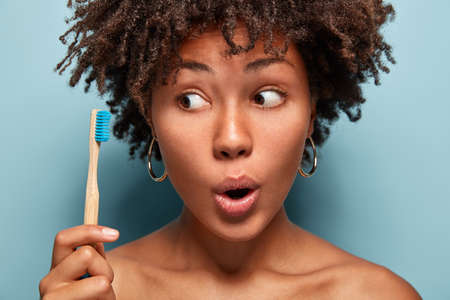 Healthy wondered woman shows wooden toothbrush, has curly hairstyle, keeps mouth opened, does everyday morning routine, daily oral care, surprised to have problems with teeth. Personal hygiene Banco de Imagens