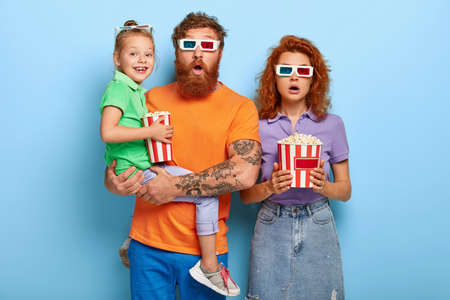 Friendly family of mum, dad and child visit film festival in cinema, watch psychological thriller or horror film, wear 3d glasses, eats fast food from bucket. Redhead three spectators enjoy movie Stock Photo