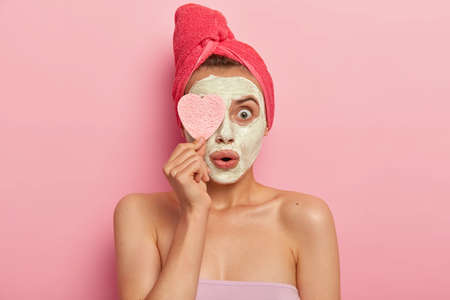Facial treatment and spa concept. Astonished young woman applies clay mask, shocked with quick effective result, keeps cosmetic sponge on eye, stands naked against pink background, heals skin