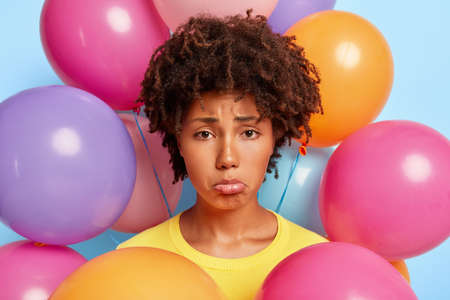 Headshot of sad desperate Afro woman purses lower lip, being in bad mood during party, has no friends wants to celebrate in big company her birthday makes photo near colorful balloons. Spoiled holiday