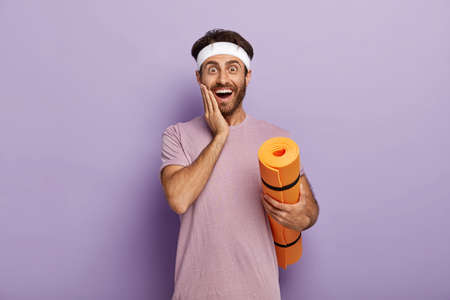 Positive Caucasian man stands with rolled up karemat, touches cheek, wears headband and t shirt, stands against purple background has fitness workout regularly, waits for coach, motivated for training Banque d'images
