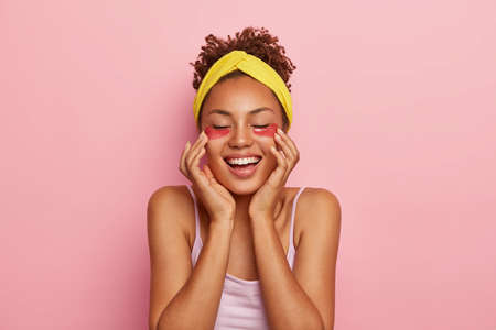 People, ethnicity, pleasure, beauty and satisfaction. Cheerful dark skinned young woman applies hydrogel flakes, reduces wrinkles and dark circles, wears yellow headband on head, has fresh skin
