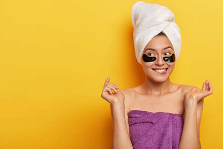 Isolated shot of pleased Caucasian woman gets pleasure from beauty treatments, has problematic skin type, wears hydrogel patches under eyes, reduces impurities and puffiness, copy space on yellow wall