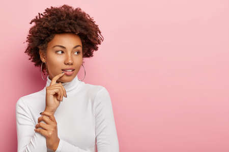 Thoughtful dark skinned woman with Afro haircut, looks aside, contemplates about something, wears white poloneck sweater, big round earrings, notices something, isolated over pink background