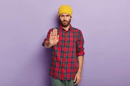 Photo of serious stern unshaven man shows stop gesture, dressed in fashionable clothes, refuses something, asks not to do forbidden actions, isolated over purple background. Body language concept